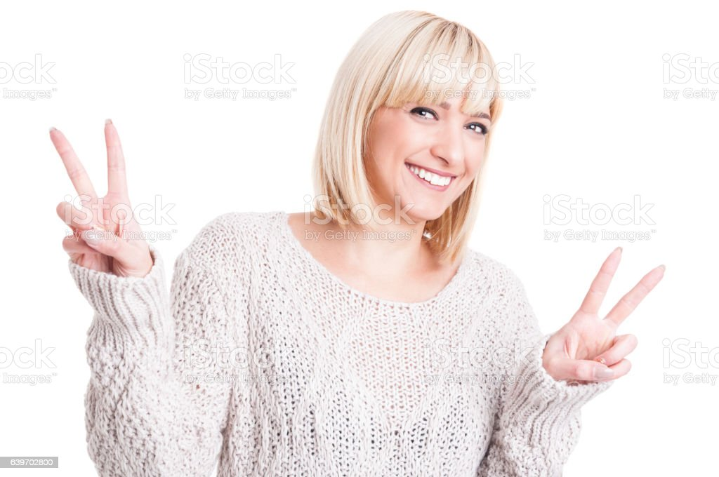 Pretty woman wearing warm sweter showing double peace stock photo