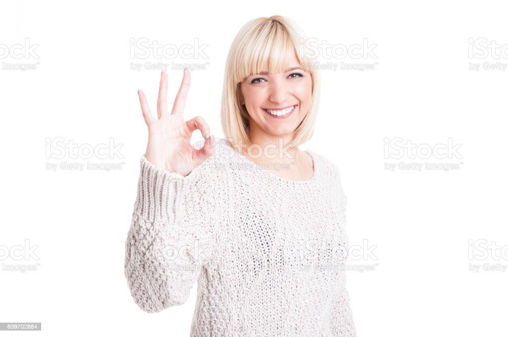 Pretty woman wearing warm sweter showing okay gesture stock photo
