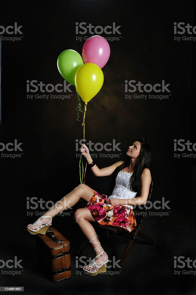 Pretty Woman With Boquet Of Pastel Balloons And Suit Case stock photo