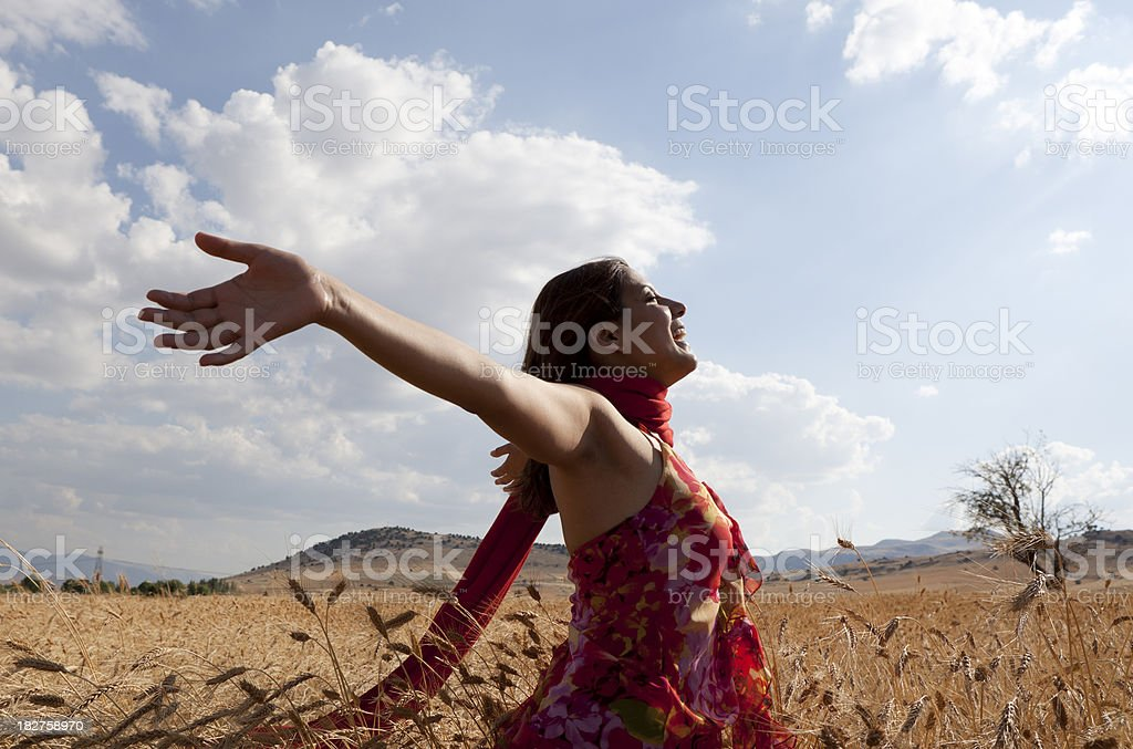 Pretty woman with flying shawl  in golden organic wheat field stock photo