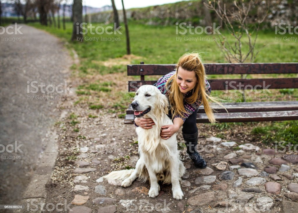 Pretty woman with her Golden Retriever Dog at a park - Royalty-free Adult Stock Photo