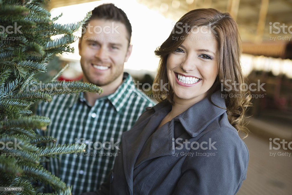 Pretty woman with husband selecting Christmas tree at farm royalty-free stock photo