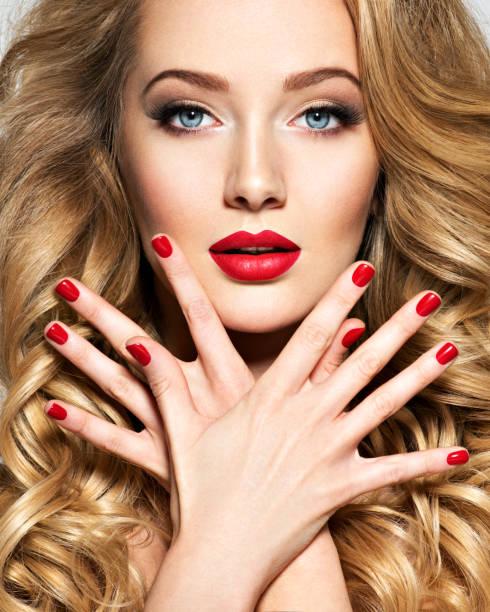 Hübsche Frau mit langen Haaren und roten Nägeln – Foto