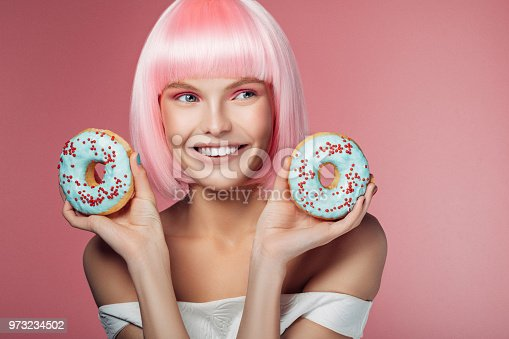692840848istockphoto Pretty woman with pink hairstyle holding multi-colored donuts 973234502