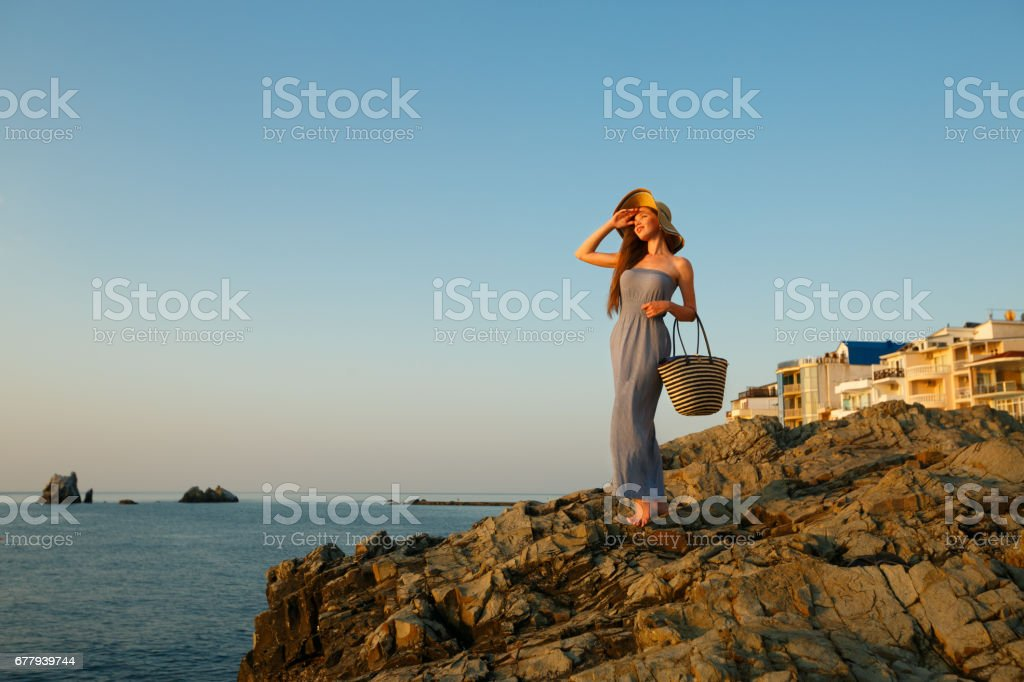 ebf826dd4ca7 Pretty woman with summer beach dress on stands on a rock beach and enjoys  sun on vacation. Attractive beautiful girl with white straw hat looking away  at ...