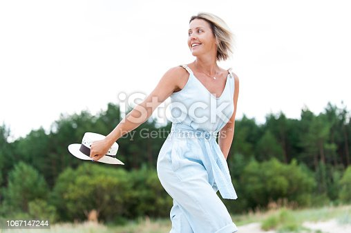Pretty woman holding summer hat enjoying sweet summer day. Outdoors summertime horizontal colored image