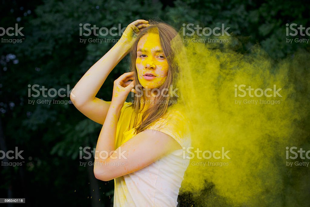 Pretty woman with yellow powder blowing in her face Lizenzfreies stock-foto
