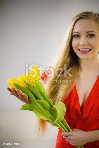 International women day, eight march. Beautiful portrait of pretty woman blonde hair with yellow tulips, fashion make up, elegant dress. Mothers day.