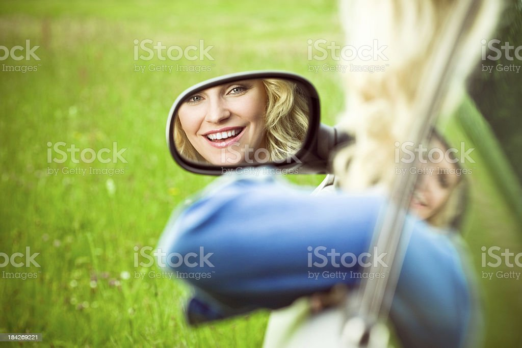 Pretty woman's reflection in side view mirror royalty-free stock photo