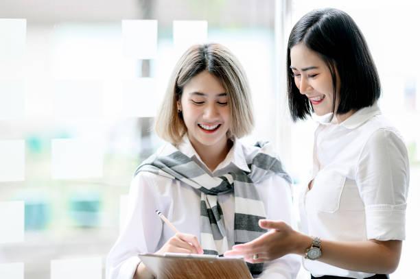 現代のオフィスで幸せと彼らの新しいプロジェクトについて議論しているかわいい女性。 - 談笑する ストックフォトと画像