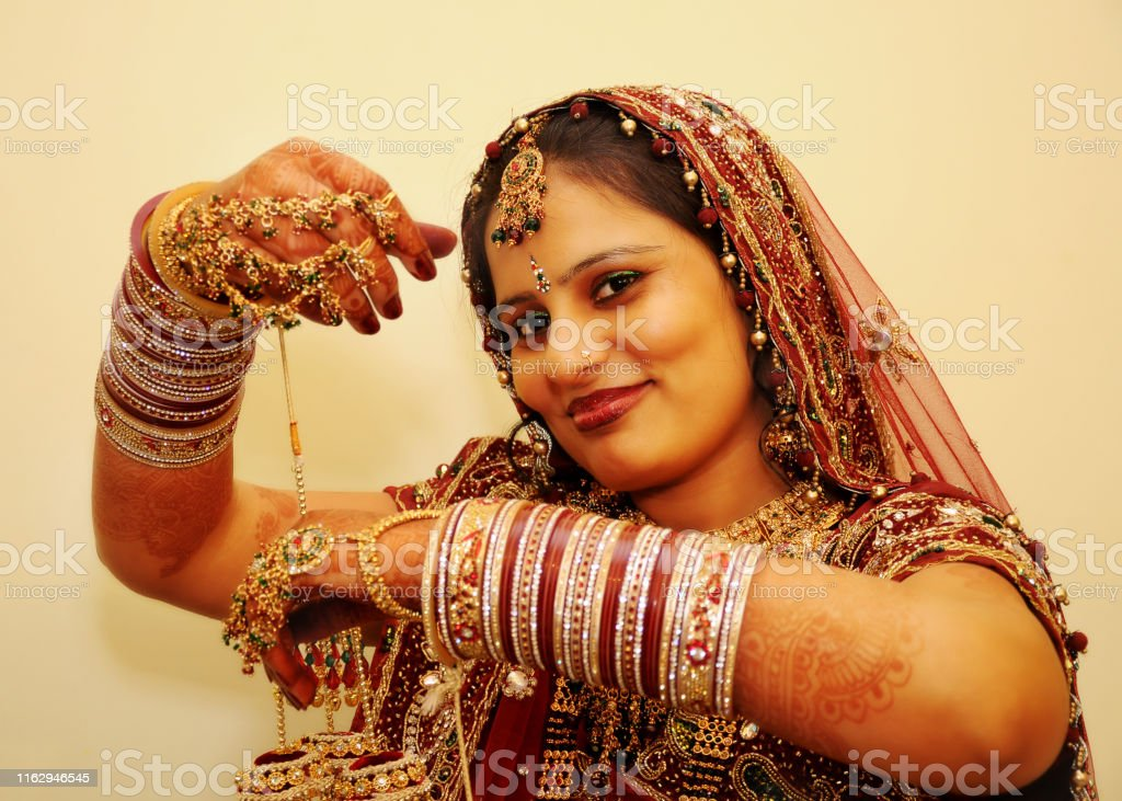 Cheerful pretty women of Indian ethnicity portrait in bride costume.