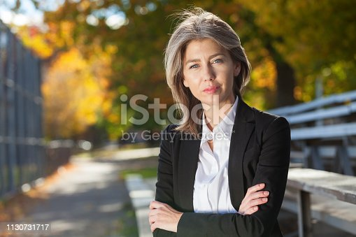 Pretty worried woman at the park. Serious Middle Aged woman