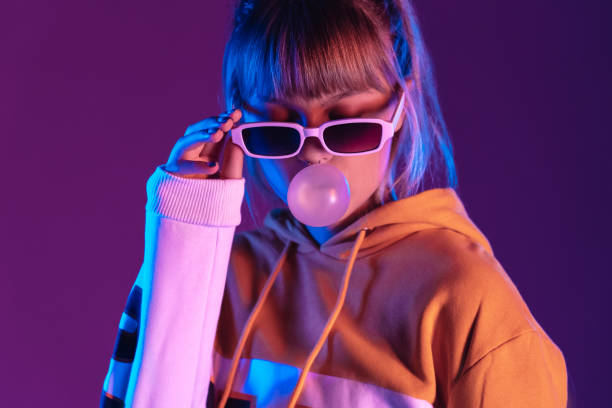pretty young 20s fashion teen girl model wear stylish glasses hoodie blowing bubble gum standing at purple violet studio wall background, igen teenager in trendy night party glow 80s 90s concept - pics for cool girl stock pictures, royalty-free photos & images