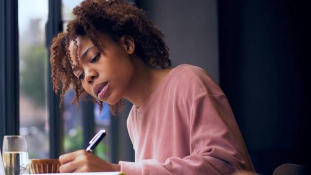 pretty young African woman writing indoor stock photo