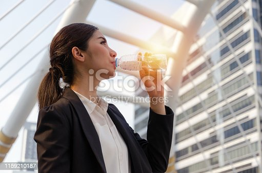 pretty young asian business woman wearing modern black suit drinking natural water for refresh yourself with modern city background, business advertising, lifestyle, good healthy and summer concept