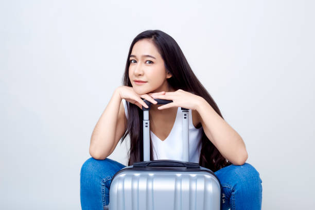 Cтоковое фото Pretty young asian woman holding passport and glass with suitcase and thinking about something. Isolated on white background