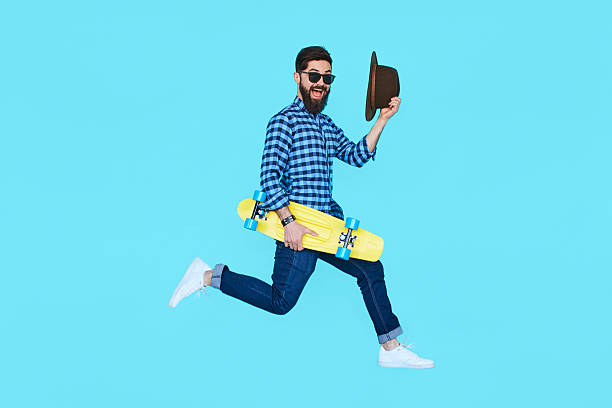 pretty young bearded man jumping with yellow skateboard - hipster persona foto e immagini stock