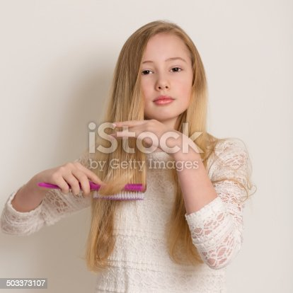 625205382 istock photo Pretty Young Blond Girl Brushing Her Hair 503373107