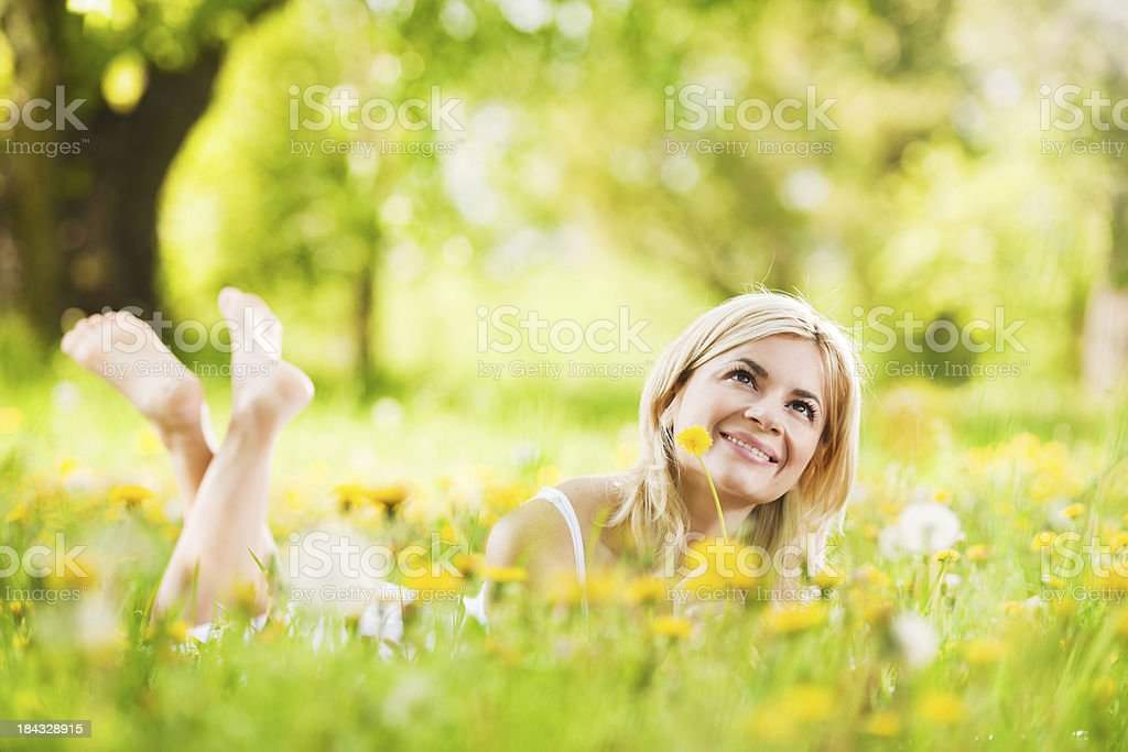 Pretty young blonde lying down in the park. royalty-free stock photo
