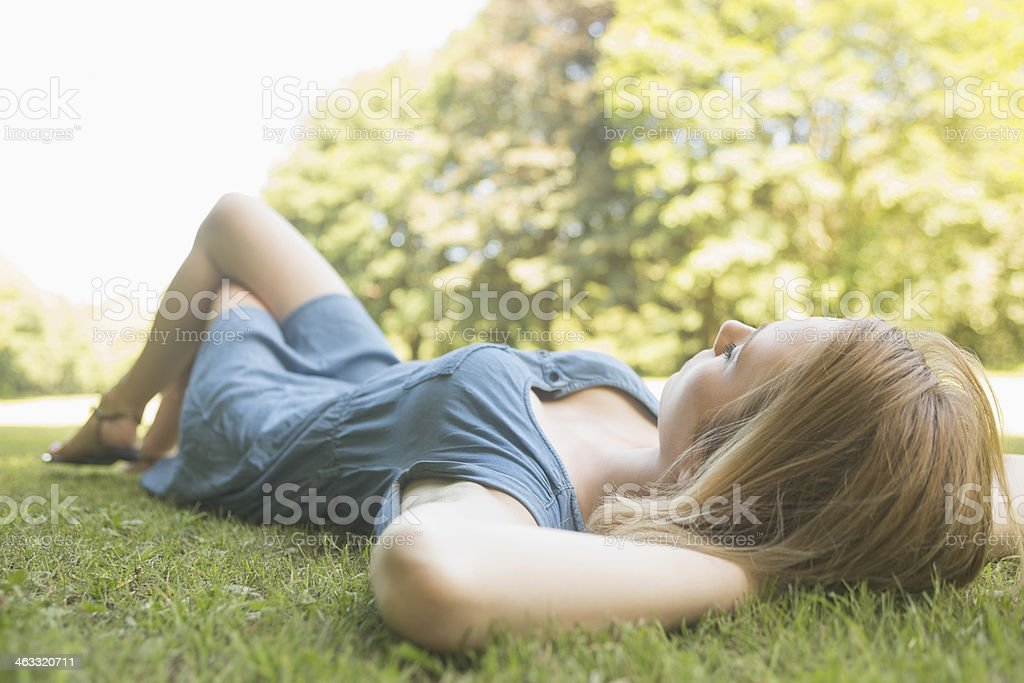 Pretty young blonde lying on the grass royalty-free stock photo