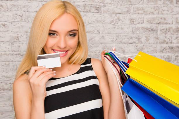 hübsche junge blondine mit einkaufstaschen und bankkarte - geld schön verpacken stock-fotos und bilder