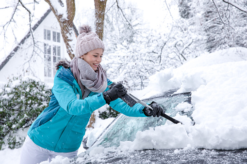 istock Pretty young blonde woman in winter sheds the white snow in front of her house on a big pile 1091853970