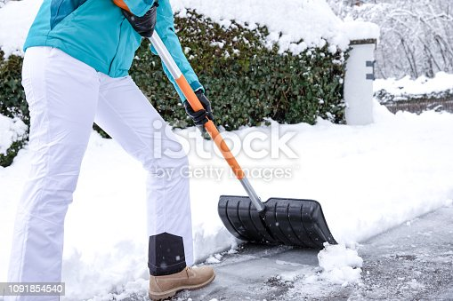 Pretty young blonde woman in winter sheds the white snow in front of her house on a big pile - dressed in cold weather blue jacket and cap she smiles happily