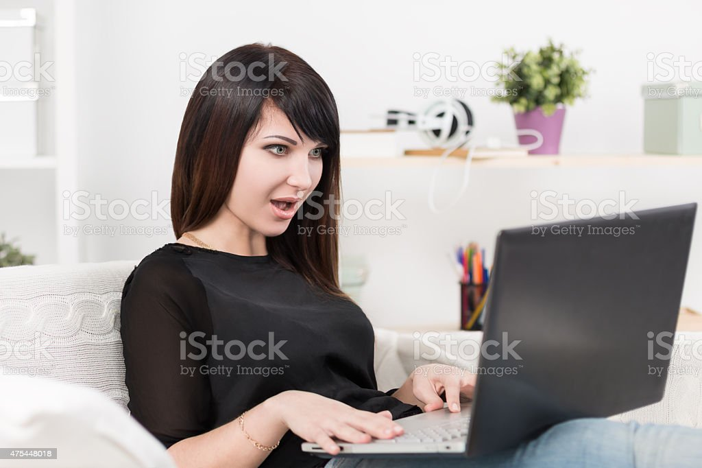 Pretty young brunette typing in laptop stock photo