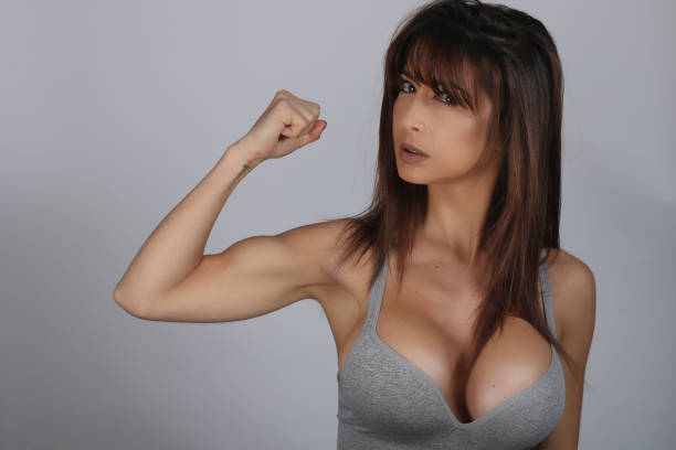 Pretty young brunette woman showing bicep on her arm stock photo