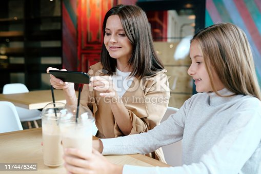 Pretty young brunette woman with smartphone taking photo of two milk cocktails in cafe while spending time with her daughter