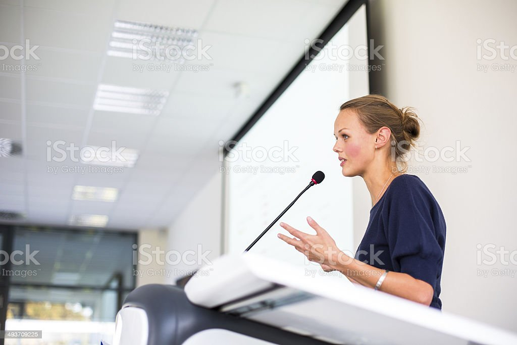 Pretty, young business woman giving a presentation stock photo
