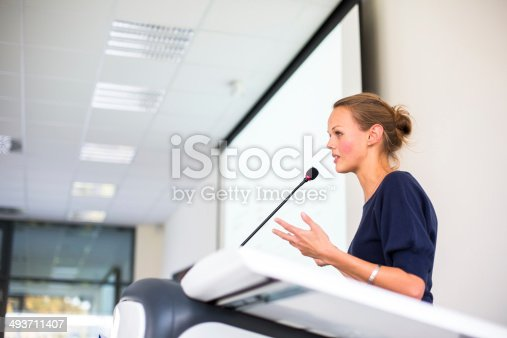 istock Pretty, young business woman giving a presentation 493711407