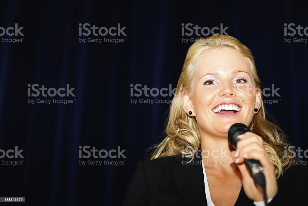 )Pretty young business woman giving a speech on stage royalty-free stock photo