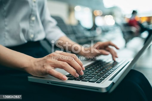istock pretty young business woman using her laptop in the train station. 1268042837