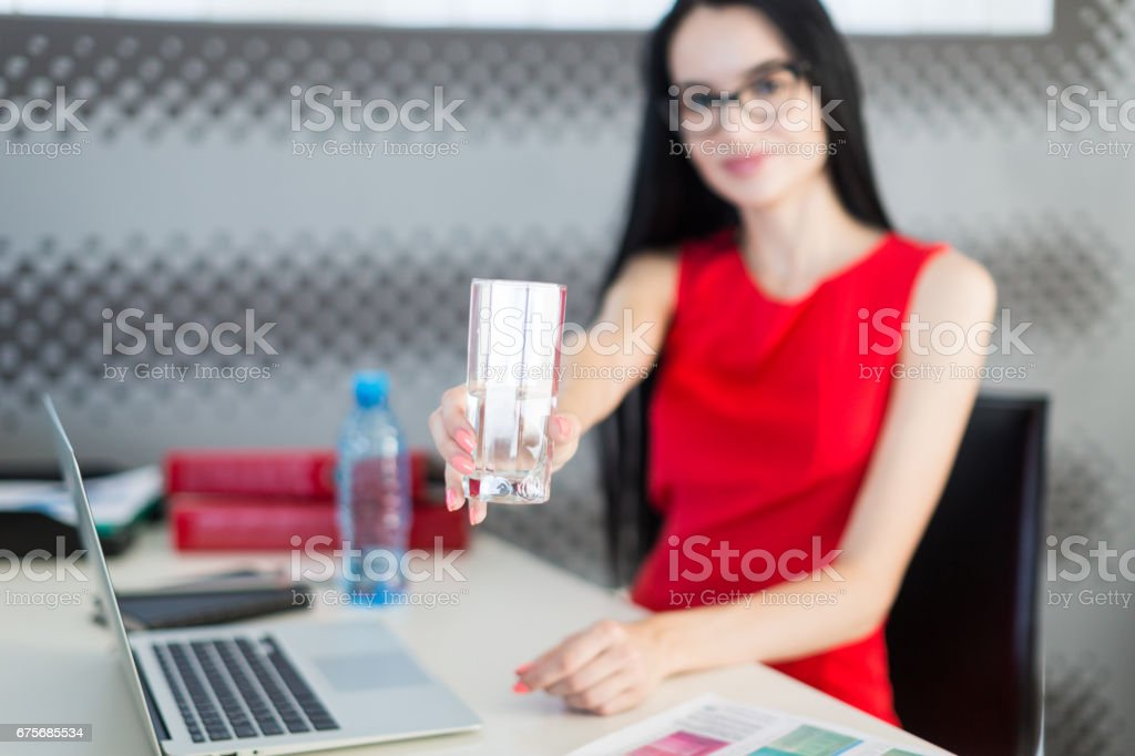 Pretty, young businesslady in red dress and glasses sit at the table and work royalty-free stock photo