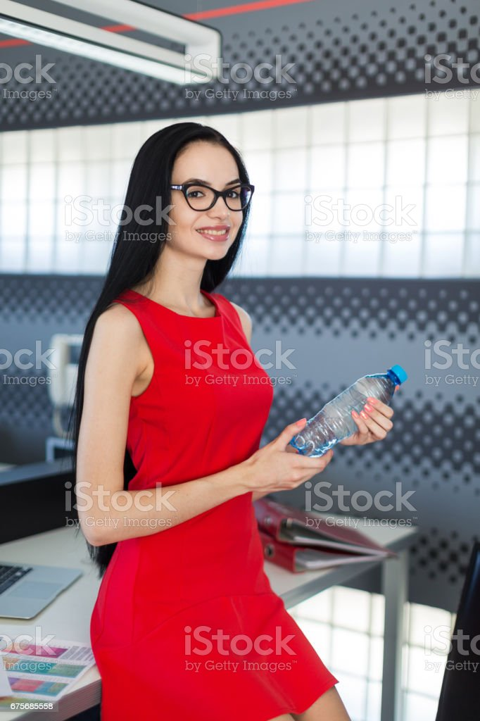 Pretty, young businesslady in red dress and glasses sit on table in the office and hold water bottle royalty-free stock photo