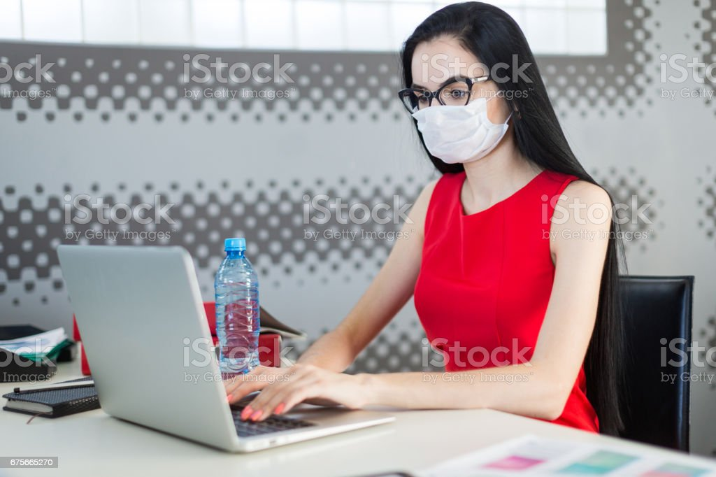 Pretty, young businesslady in red dress, gas mask and glasses sit at the table and work royalty-free stock photo
