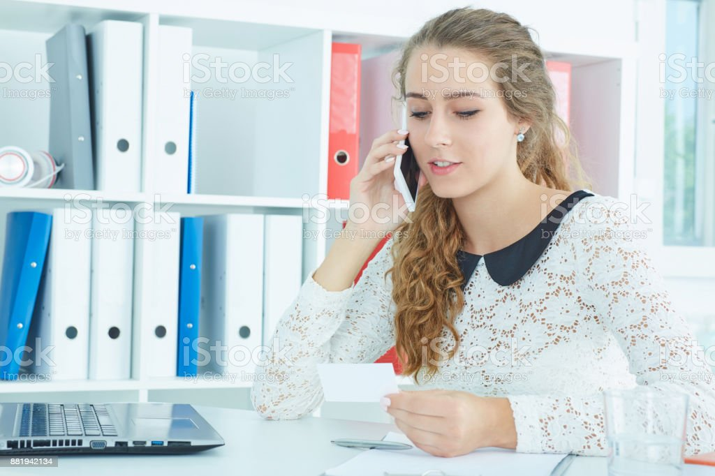 Pretty young caucasian woman holding phone and bisness card using laptop. stock photo