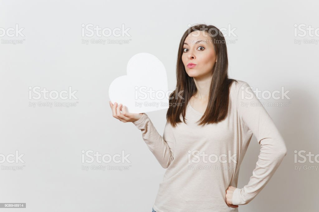 Pretty young cheerful woman holding big white heart in hands isolated on white background. Copy space for advertisement. With place for text. St. Valentine's Day or International Women's Day concept. stock photo