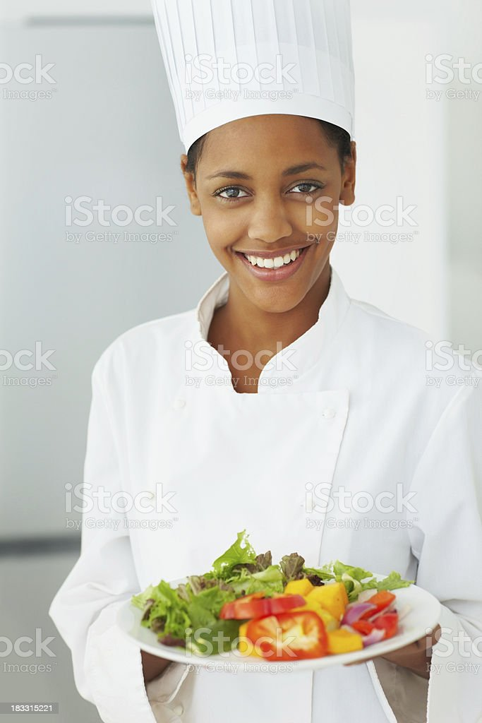 Pretty young chef holding a fresh salad dish royalty-free stock photo