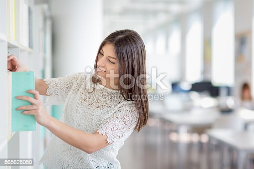 929797156 istock photo Pretty, young college student looking for a book in the library 865628080