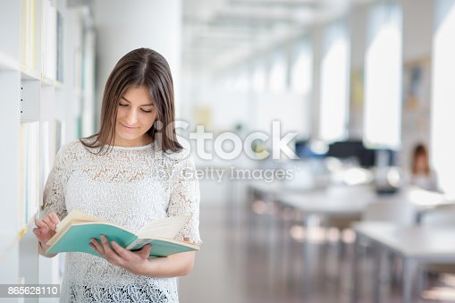 929797156 istock photo Pretty, young college student looking for a book in the library 865628110