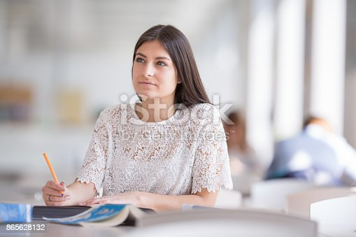 929797156 istock photo Pretty, young college student looking for a book in the library 865628132