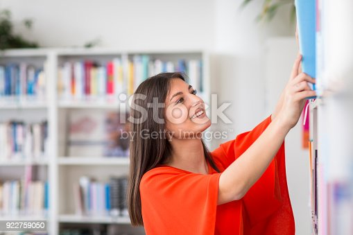 929797156 istock photo Pretty, young college student looking for a book in the library 922759050