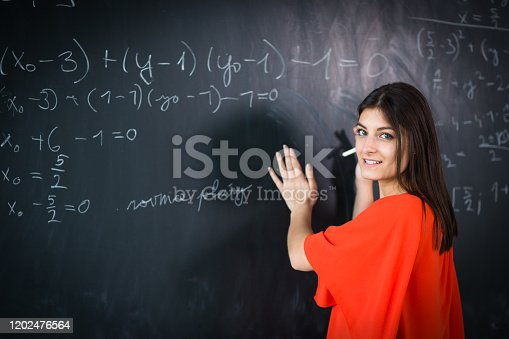 922759140 istock photo Pretty, young college student writing on the chalkboard 1202476564