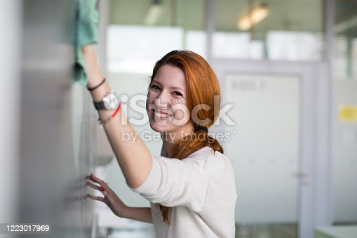 922759140 istock photo Pretty young college student writing on the chalkboard 1223017969