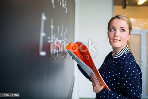 929797156 istock photo Pretty, young college student writing on the chalkboard 929797156