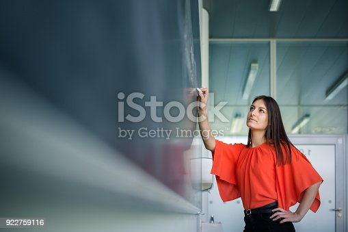 922759140 istock photo Pretty, young college student writing on the chalkboard/blackboard 922759116