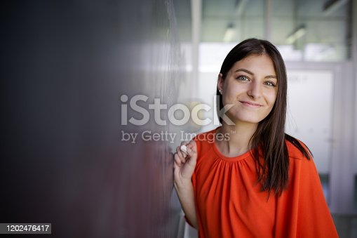 922759140 istock photo Pretty, young college student/young teacher writing on the chalkboard 1202476417