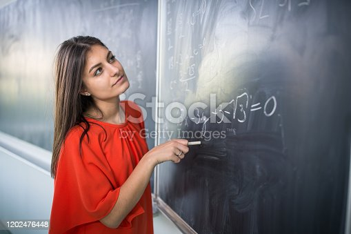 922759140 istock photo Pretty, young college student/young teacher writing on the chalkboard 1202476448